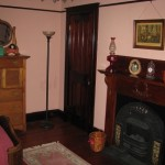 Mantel, closet door, throw rug and antique dresser can be seen in this view
