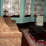 Victorian-look sofa with end table on throw rug with bay windows covered with lace curtains is shown