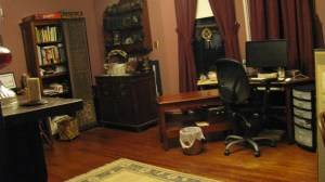 large office with hard wood floor, tall windows, wood furniture and bookshelves