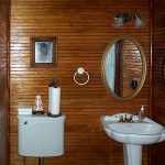 Finished beadboard wall with oval mirror, towel ring, high tank antique toilet and replica pedestal sink