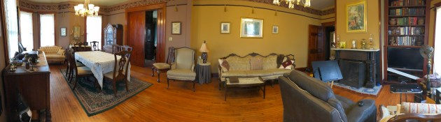 Room with light-plum walls on one side and gold walls on other, four tall lit windows seen to far left, shiny wood pocket door, dark wood picture rails and dark wallpaper trims top of room with pictures hanging, room is furnished with Victorian-style seatings and diningroom table, fireplace with white marble mantle to right, dark wood floors