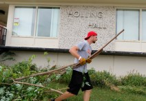 Dean Penner carries tree branch in front of Holling Hall.