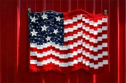 Flag quilt displayed on red barn siding.