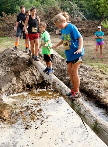 Abby Brevin and Kim Leggott balance on pole across pit of muddy water. Washington County Rodeo Saturday.