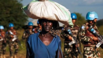 A displaced woman carries goods as United Nations Mission in South Sudan (UNMISS) peacekeepers patrol outside the premises of the UN Protection of Civilians site in Juba. /Albert Gonzalez Farran/AFP/Getty Images
