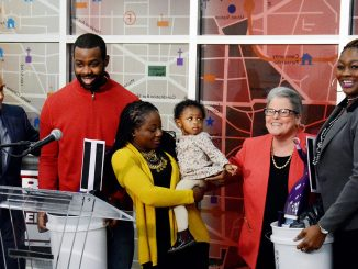 "Brian Kenner (left), Polly Donaldson (second from right) and Jeanette Station (right) stand with new homeowners Johnathan and Precious Tate and their young daughter during Mayor Bowser's ""Home for the Holidays: Celebrating the Gift of Homeownership"" on Monday, Dec. 12 at the DCHD headquarters in Southeast."