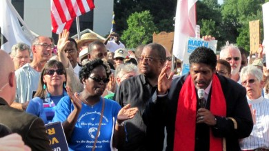 Rev. Dr. William Barber II (right), the president of the N.C. state branch of the NAACP, speaks at a Moral Mondays rally in 2013.
