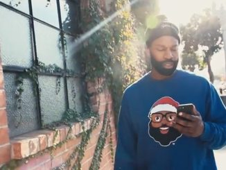 Former NBA superstar Baron Davis wears a sweater bearing his company's Black Santa logo.