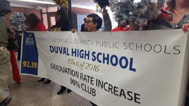 Prince George's County Public Schools officials hold a banner congratulating last year's senior class at DuVal High School in Lanham for having a 92 percent graduation rate. Central office personnel including schools CEO Kevin Maxwell visited several schools Feb. 8 to celebrate the high graduation rates. (William J. Ford/The Washington Informer)