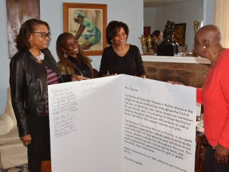 From left: Zillah F. Jackson-Wesley, Sylvia Bennett, Vanilla Jackson-Crawford and Anita Shelton of DC Women In Politics prepare a welcome card to former first lady Michelle Obama. (Roy Lewis/The Washington Informer)
