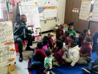 Kelly Gilmore, member of the Omicron Lamda Alpha chapter of Alpha Phi Alpha Fraternity Inc, reads to a class of first-graders at Orr Elementary School in Southeast after the organization donated over 300 books to its library on March 17. (Courtesy photo)