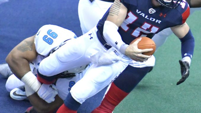 Washington Valor quarterback Sean Brackett is tackled by Philadelphia Soul defensive lineman Justin Lawrence during Philadelphia's 48-47 win at Verizon Center in D.C. on May 27. (John E. De Freitas/The Washington Informer)