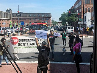 Protesters with Empower D.C. block a bus tour of developers speculating in Anacostia on April 19. (Courtesy of The Washington Business Journal)