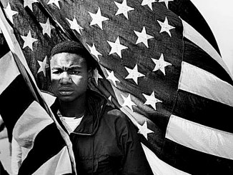 "Lewis ""Big June"" Marshall Carrying the U.S. Flag, Selma to Montgomery March on March 21, 1965 (Courtesy of the estate of James Karales)"