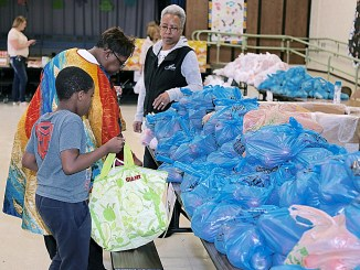 Sarah Stepherson (center) stands beside her grandson next to a table covered with dozens of apples at H. Winship Wheatley Early Childhood Center in Capitol Heights on May 3 as she collected food provided by the Capital Area Food Bank. (Demetrious McKinney/The Washington Informer)