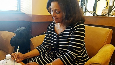 Veronica Davila, president of the Prince George's County chapter of the Hearing Loss Association of American, takes notes while talking with members of the organization at a Wegman's in Lanham on June 28 as her dog, Sammie, looks on. (William J. Ford/The Washington Informer)