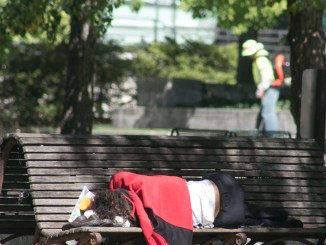 A homeless woman sleeps on a bench in front of the Canadian Embassy. (Shevry Lassiter - The Washington Informer)