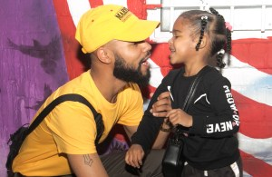 Hip Hop artist Chaz French who recently signed with Motown, directs his attention to his daughter Akai, 4 after an interview with the Washington Informer. /Photo by Shevry Lassiter