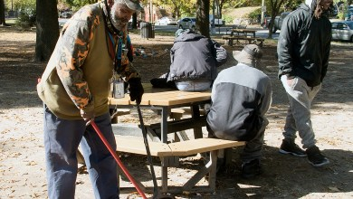 """Ricardo """"Two Canes"""" Taliaferro, a resident of Southeast, tries to keep Shepherd Park clean by sweeping up the area located at the gateway of the Congress Heights commercial district in Southeast. (Shevry Lassiter/The Washington Informer)"""