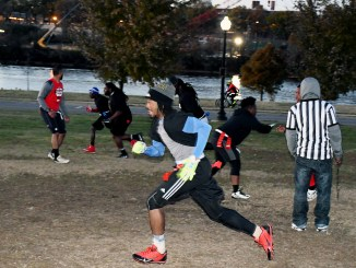 Officers from the Metropolitan Police Department play flag football with youth from the community on Nov. 17 at Anacostia Park in Southeast to help improve police-community relations. (Roy Lewis/The Washington Informer)