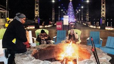 """Bobbi Lancaster, fire pit attendant at The Wharf in southwest D.C., keeps things """"fired up"""" during the new family-friendly center now featuring holiday activities. (Shevry Lassiter/The Washington Informer)"""