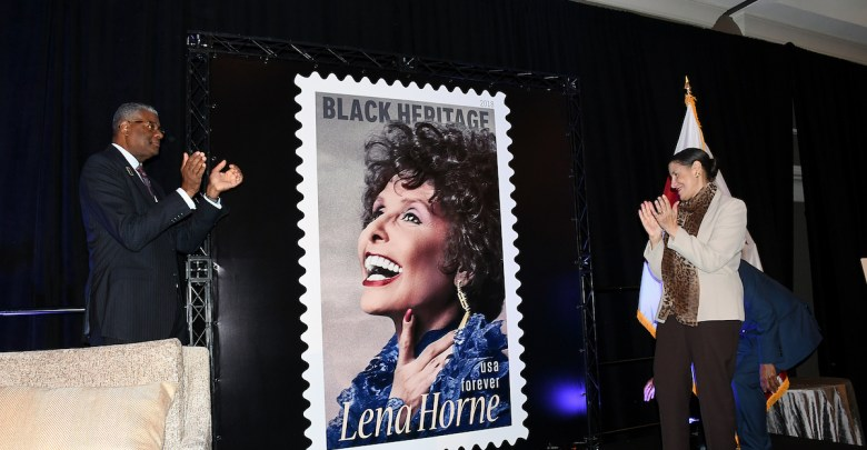 Ronald A. Stroman, deputy postmaster general of the United States, and ASALH President Evelyn Brooks Higginbotham unveil the 2018 commemorative Black Heritage stamp of Lena Horne during the 92nd annual Black History Luncheon at the Washington Renaissance Hotel in D.C. on Feb. 24. (Roy Lewis/The Washington Informer)