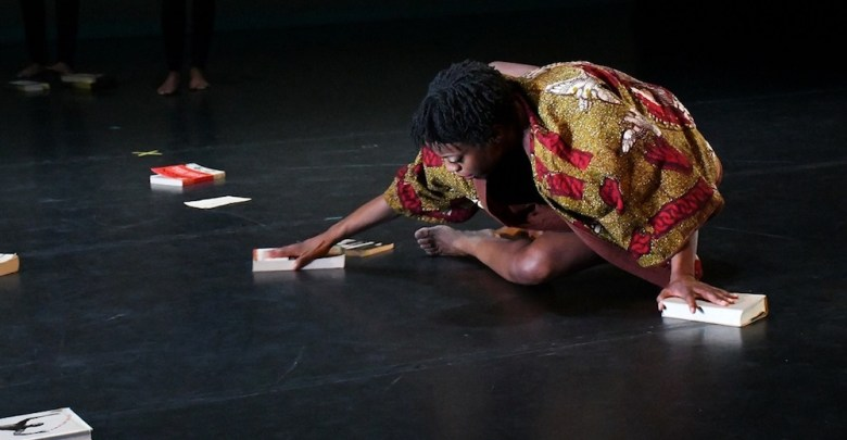"""Ronya-Lee Anderson stretches on the floor to perform a piece she created called """"Canon"""" during a dress rehearsal at the Clarice Smith Performing Arts Center in College Park on Jan. 26. (Roy Lewis/The Washington Informer)"""