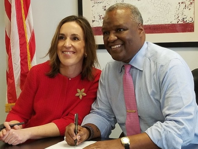 Prince George's County Executive Rushern L. Baker III signs documents to officially declare his candidacy for Maryland governor on Feb. 20, alongside running mate Elizabeth Embry. (William J. Ford/The Washington Informer)