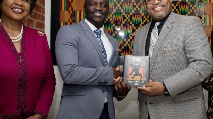 "Jesse L. Holland (right), author of the book ""Black Panther: Who Is the Black Panther?"", presents singer Akon (center) with a copy of the book as Arikana Chihombori-Quao, African Union Ambassador to the U.S., poses with them for a photograph at the Africa House in northwest D.C. (Shevry Lassiter/The Washington Informer)"