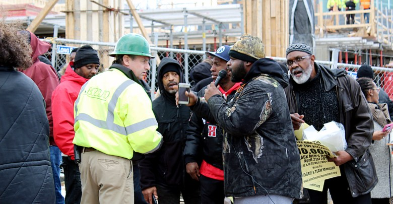 Benji Little (center), holding a cellphone and microphone, joins a group of demonstrators at the Big Chair in southeast D.C. to confront a Bozzuto construction manager on March 8 in an effort to stop what many area residents see as unfair development in the ward. The demonstrators, including Ward 8 Council member Trayon White were able to shut down construction on Maple View Flats project for half a day. (Brigette White/The Washington Informer)