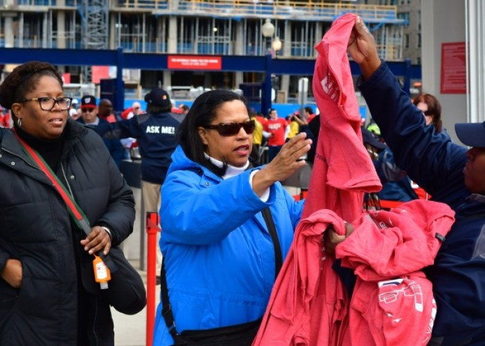 A Nationals Park employee distributes T-shirts adorned with the Washington Nationals' 2018 schedule to fans entering the stadium in southeast D.C. prior to the team's home opener against the New York Mets on April 5. (John E. De Freitas/The Washington Informer)