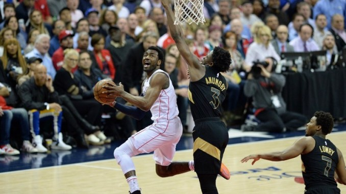 Washington Wizards point guard John Wall attempts a shot over the outstretched arm of Toronto Raptors forward OG Anunoby during the Raptors' series-clinching 102-92 win in Game 6 of the Eastern Conference first-round playoff series at Capital One Arena in D.C. on April 27. (Reggie Hildred/Special to The Informer)