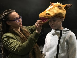 "Costume designer Claudia Brownlee helps cast member Sia Li Wright adjust her camel costume for ""One Lonely Camel,"" one of four stories in ""Pop-Up Books"" being presented April 19 at the Anacostia Playhouse. (Courtesy of Anacostia Playhouse)"