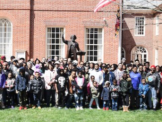 """AAHT participants gather around the statue of Frederick Douglass on the front lawn of the Talbot County Courthouse in Cambridge, Maryland, where he delivered the """"Self-Made Men"""" speech to a segregated audience in the courthouse on Nov. 25, 1878. The statue was created by Jay Hall Carpenter and erected in 2011. (Roy Lewis/The Washington Informer)"""