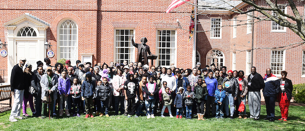"AAHT participants gather around the statue of Frederick Douglass on the front lawn of the Talbot County Courthouse in Cambridge, Maryland, where he delivered the ""Self-Made Men"" speech to a segregated audience in the courthouse on Nov. 25, 1878. The statue was created by Jay Hall Carpenter and erected in 2011. (Roy Lewis/The Washington Informer)"