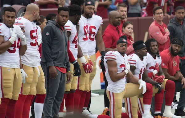 **FILE** Members of the San Francisco 49ers, including safety Eric Reid (35), kneel during the national anthem before a game against the Washington Redskins at FedEx Field in Landover, Maryland, on Oct. 15, 2017. (Keith Allison via Wikimedia Commons)