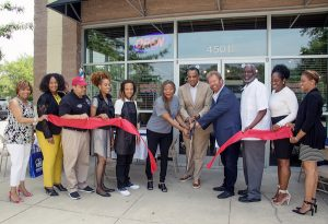 Entrepreneurs Jim and Deborah Guynn, to the right and left of Prince George's County Chamber of Commerce President & CEO David Harrington, and barbershop staff, cut the ribbon at the grand opening of Distinctive Hair & Grooming for Men in Mitchellville, Md., on June 8. (Shevry Lassiter/The Washington Informer)