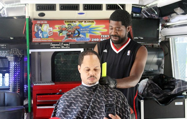 """Emmanuel """"E-Man"""" Azoro, also known as """"The Shapeup King,"""" tends to a customer inside his mobile barbershop during the second annual Man Cave at Emery Heights Father's Day Celebration on June 16. (Courtesy of Man Cave at Emery Heights)"""