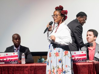 Aiyi'nah Ford, executive director of the Future Foundation, poses questions to James Butler, Dustin Canter and Ernest Johnson during a mayoral candidates' forum at Ballou Senior High School in southeast D.C. on June 6. (Shevry Lassiter/The Washington Informer)