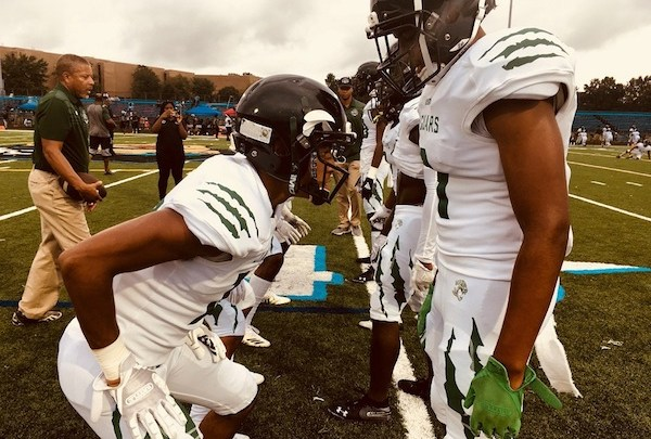 Members of Charles H. Flowers High School's football team line up on the field before a recent game. (Courtesy of Visionary Media Productions)