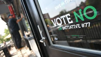 """A man stands near a """"vote no on Initiative #77"""" sign on June 18, 2018 in Washington, DC. - Washington, DC's upcoming primary election includes a ballot measure called Initiative 77, a policy to gradually raise the minimum wage that tipped workers receive. (MANDEL NGAN/AFP/Getty Images)"""