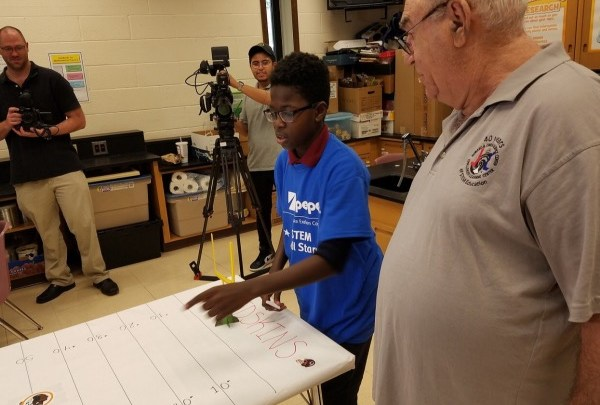 Osmon Best (center), a student at Thomas Johnson Middle School, shows instructor Richard Rubino how he plans to kick a paper football during STEM activities at the Howard B. Owens Science Center in Lanham, Maryland, on Oct. 10. (William J. Ford/The Washington Informer)
