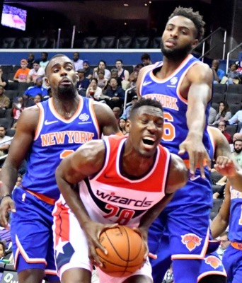 Washington Wizards center Ian Mahinmi (28) is surrounded underneath the basket by New York Knicks guard Tim Hardaway Jr. (left) and center Mitchell Robinson during the Knicks' 124-121 preseason win at Capital One Arena in D.C. on Oct. 1. (John De Freitas/The Washington Informer)