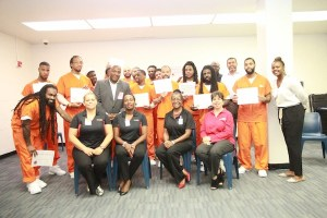 Graduates at the Correctional Detention Facility ceremony display their certificates and are flanked by Industrial Bank and DC DOC program participants. (Courtesy of DC Department of Corrections)