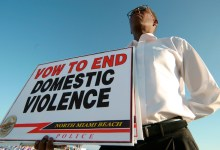 A man holding a sign at the Domestic Violence March event. (Photo by: Jeffrey Greenberg/UIG via Getty Images)