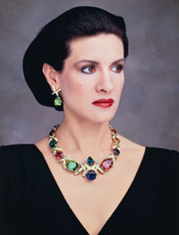 Paloma Picasso wears her bold fifth anniversary necklace (aquamarine, tanzanite, tourmaline, peridot, amethyst and topaz). The matching green tourmaline earrings also feature her signature diamond X's.
