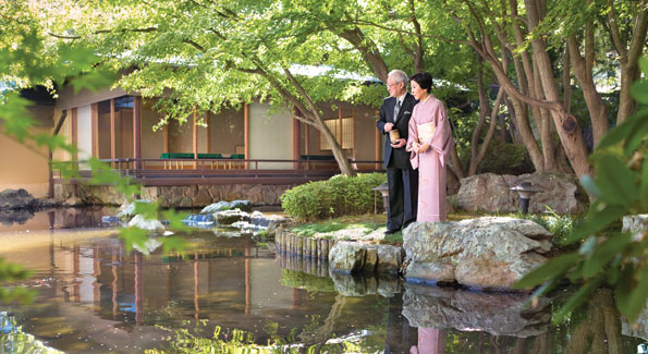 Ambassador Kato and Mrs. Kato take a moment to feed the carp in the residency's Koi pond. The tea house in the background was first built in Japan and then reassembled at the residence.