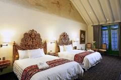 Habitación Colonial Doble: Many of the suites in the original colonial house feature cathedral ceilings and carved wooden headboards