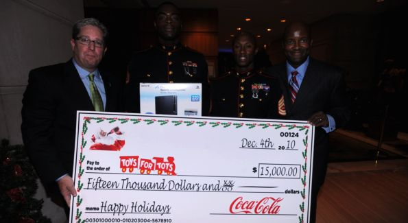 Coca Cola executives presents the check to Toys for Tots. Image courtesy of Brett Bagley.