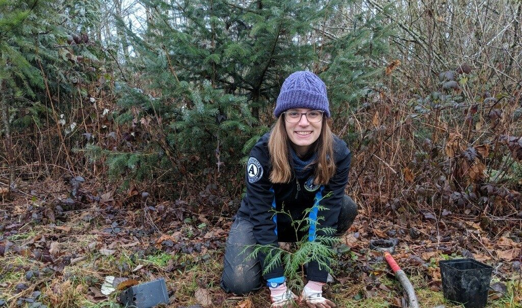 WSC member Abigail serving with Skagit Land Trust in Mt. Vernon, WA, posing with sapling in wooded area.